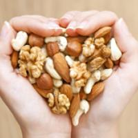 Hands cupped holding a mixture of nuts in a heart shape