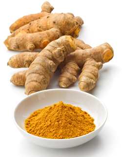Fresh turmeric and bowl of turmeric powder