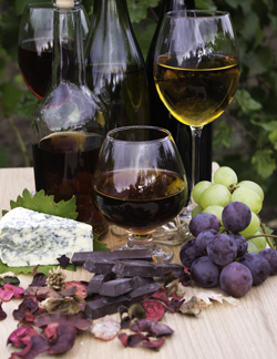 Wine glasses, fruit, chocolate, and vegan cheese display